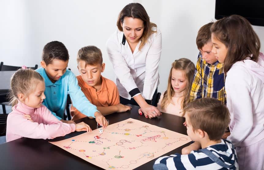 Imagem de mulher e crianças jogando em mesa.