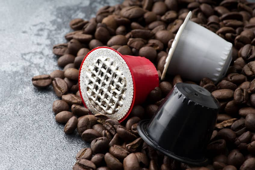 Scattered coffee beans and three coffee pods