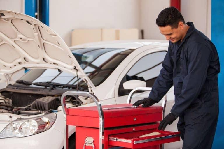 Imagem de homem trabalhando em carro com caixa de ferramentas com rodas ao lado.