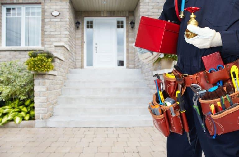 Homem em frente a uma casa segurando caixa de ferramentas.