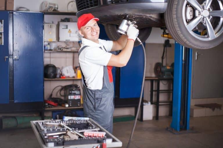 Homem trabalhando arrumando carro.