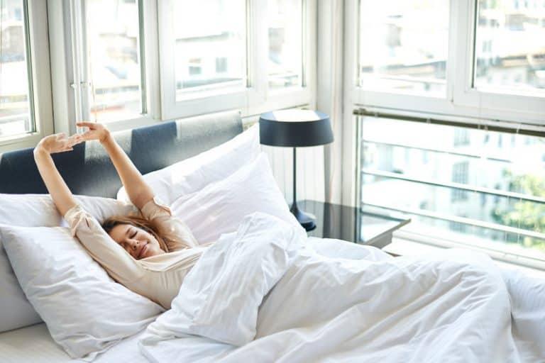 Imagem de mulher se espreguiçando na cama.