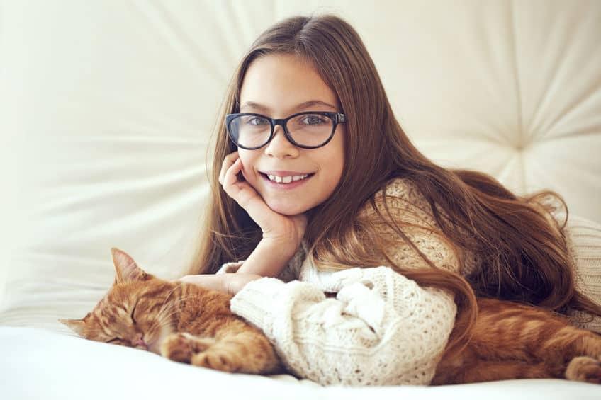 Imagem de menina e gato deitados.