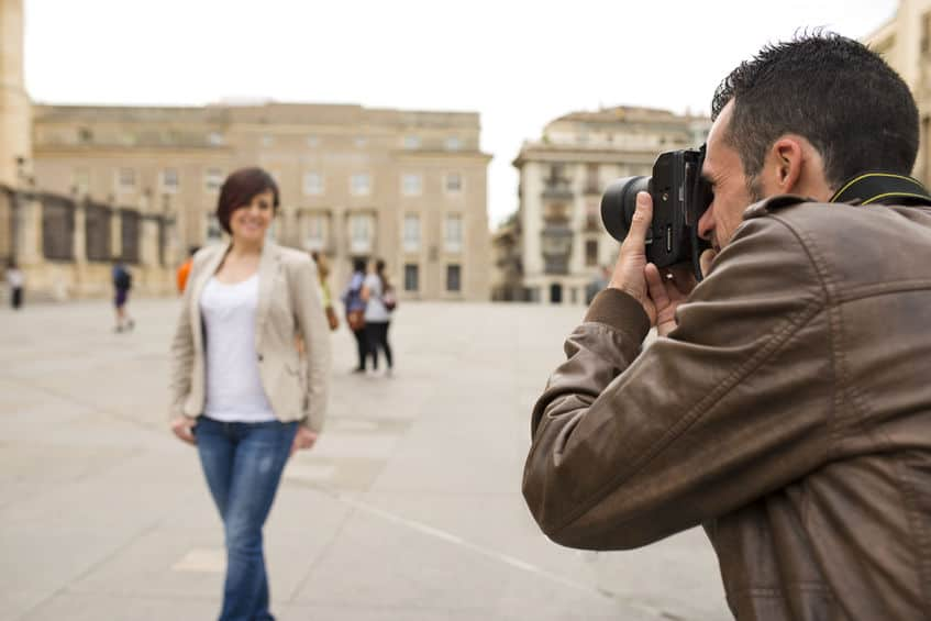 Imagem de homem fazendo foto de mulher em praça.