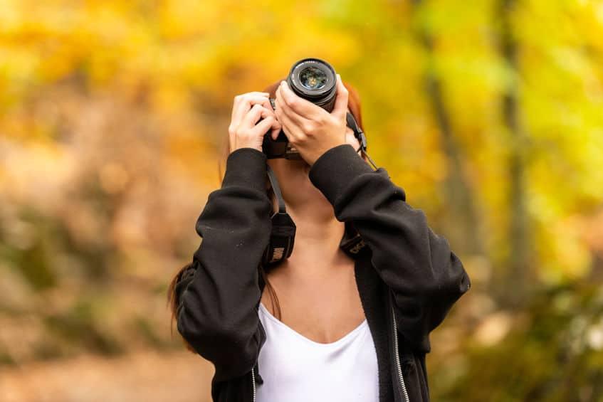 Imagem de mulher tirando fotos com câmera DSLR.