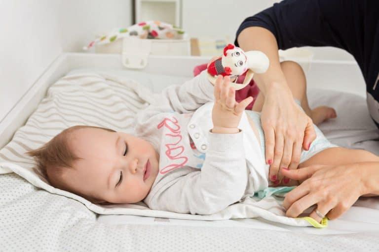 Imagem de bebê sendo trocado.