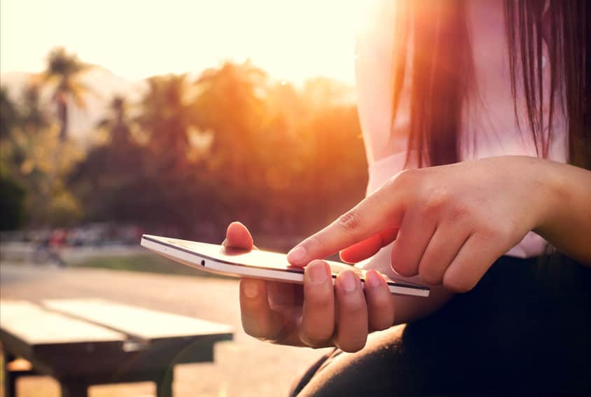 Imagem de mulher carregando celular, com por do sol ao fundo.