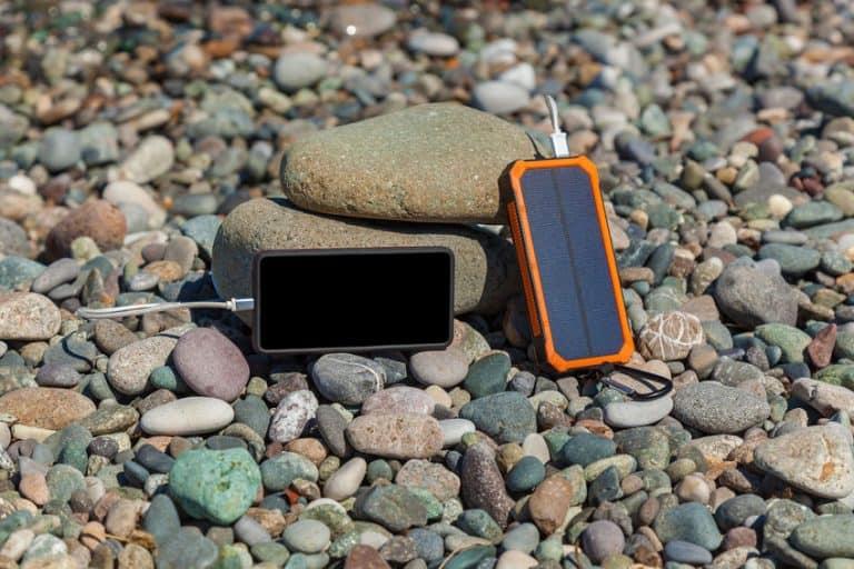 Carregador e celular sobre pedras.