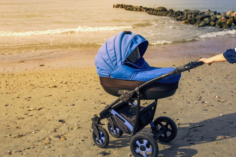 Carrinho de bebê azul na praia.