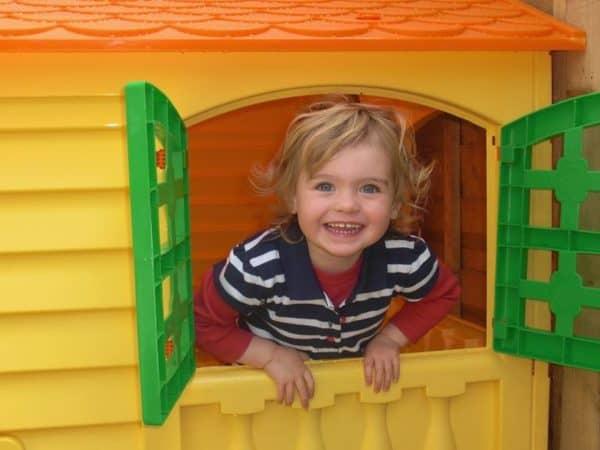 Garotinho sorridente na janela de uma casinha