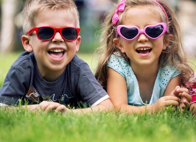 Menino e menina deitados na grama usando óculos de coração