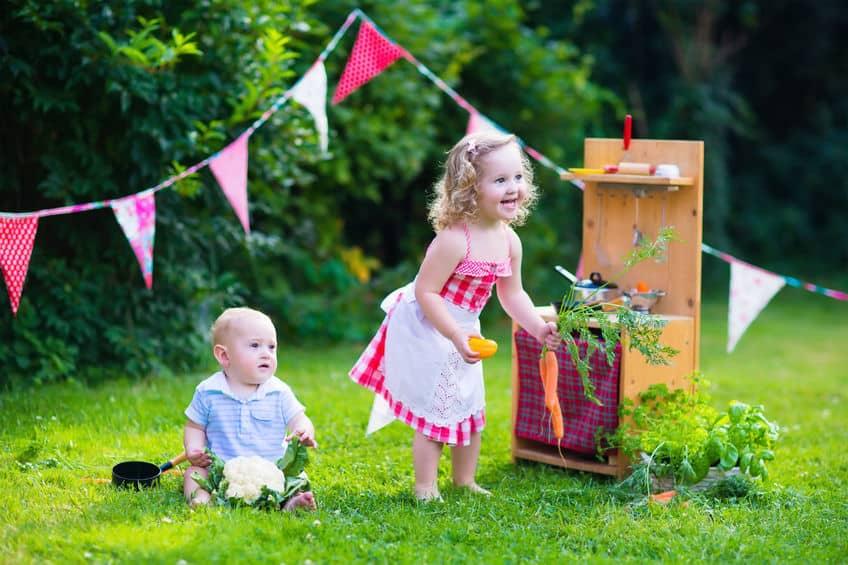 Duas crianças brincando de casinha.