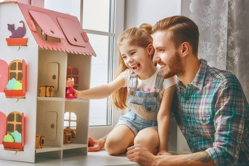 Menina brincando na casa de boneca com o pai