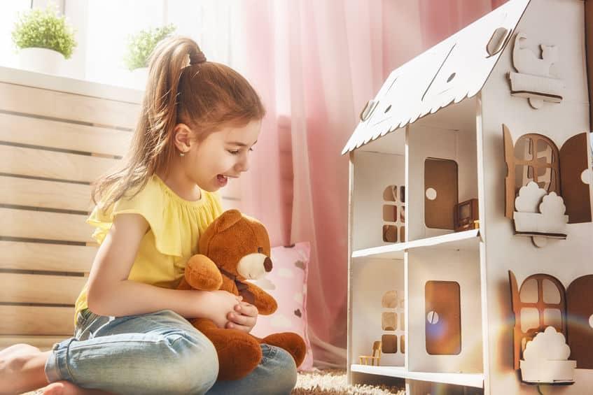 Menina brincando com casa de boneca e segurando um urso de pelúcia