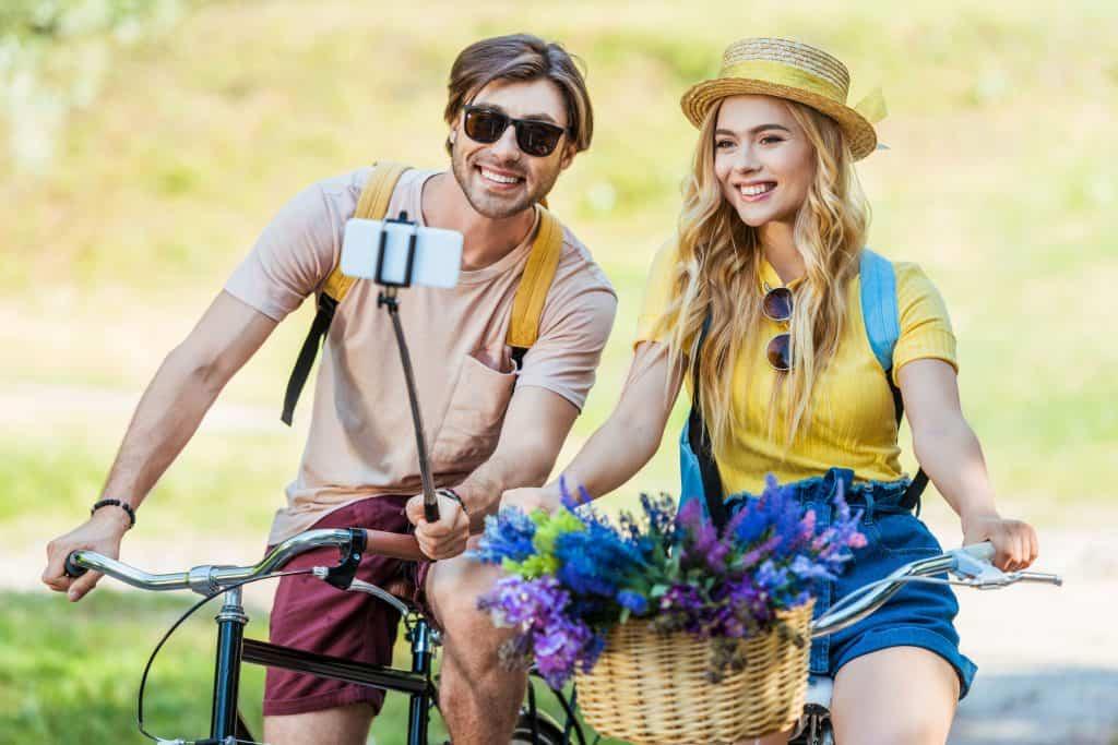 Casal andando de bicicleta e fazendo selfie.