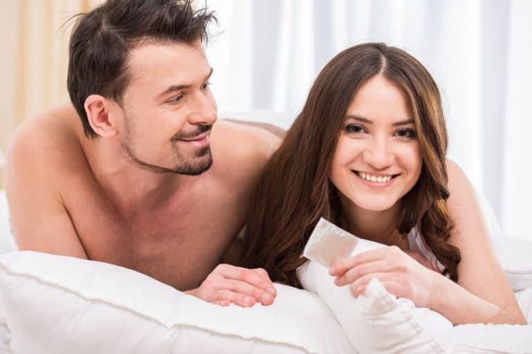 Casal feliz na cama segurando camisinha.
