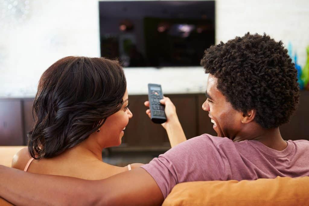 Casal no sofá assistindo TV.