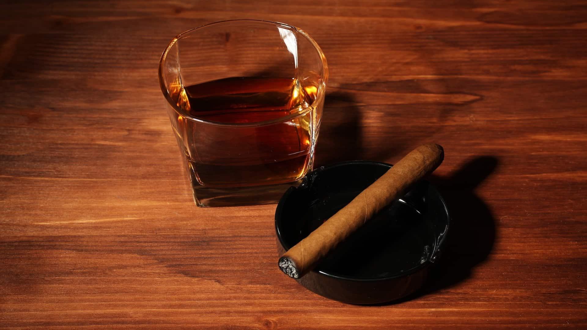 Imagem de cinzeiro e copo de whisky.