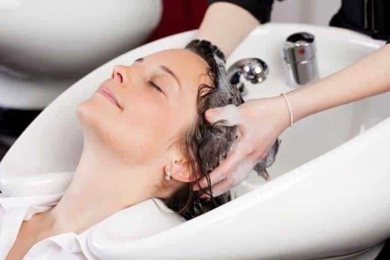 Mulher lavando o cabelo em salão de beleza.