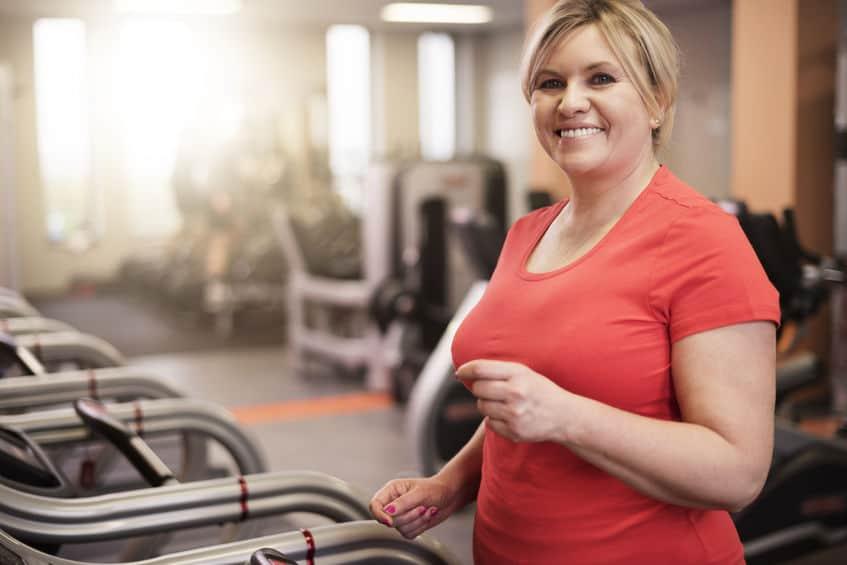 Mulher sorri enquanto se exercita na esteira