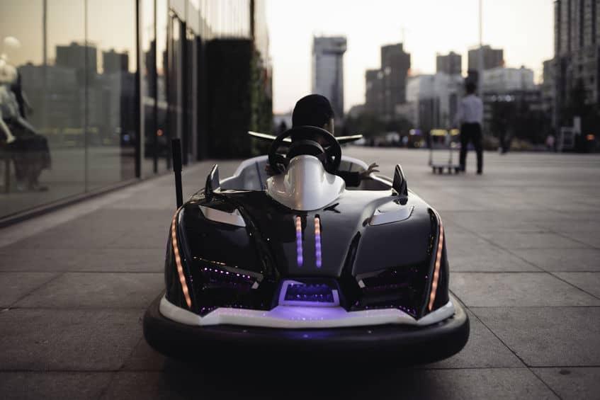 Imagem em um cenário urbano mostra um carro infantil elétrico cheio de luzes