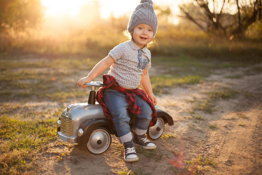 Criança sorridente sentada sobre um pequeno carrinho infantil
