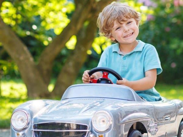 Um menino sorri enquanto dirige seu carro infantil