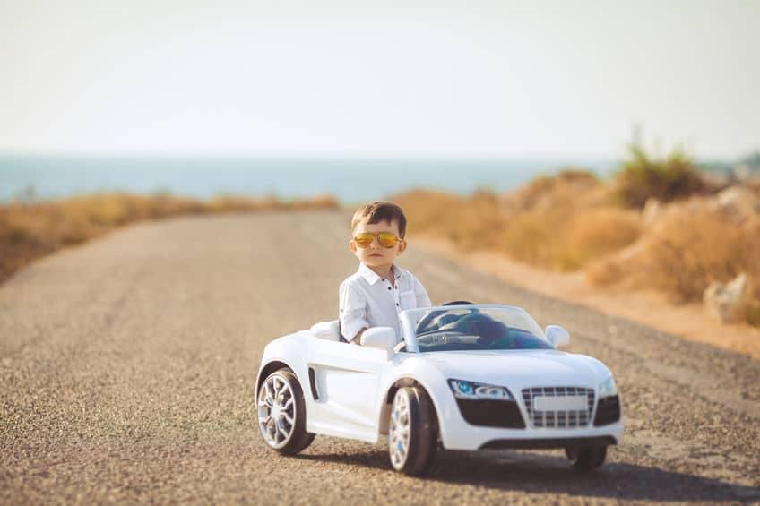 Criança em um carro infantil branco faz pose em meio a uma estrada de asfalto