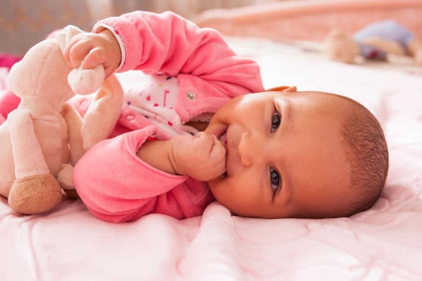 Bebê sorrindo deitado.