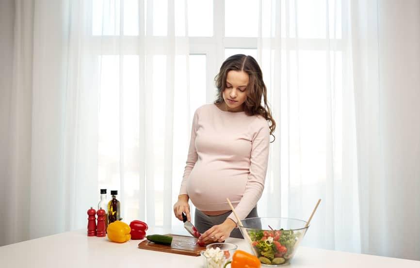 Mulher grávida preparando salada.