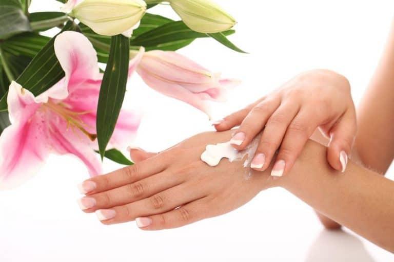 Mãos femininas passando creme com flores ao fundo.