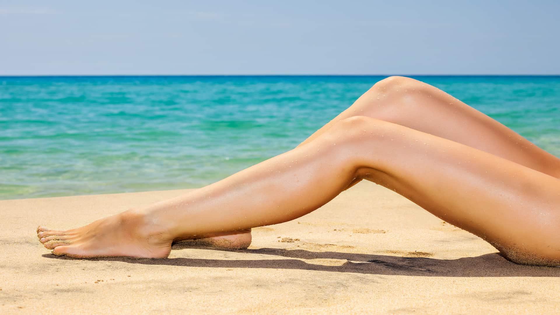 Pernas de mulher na beira do mar.