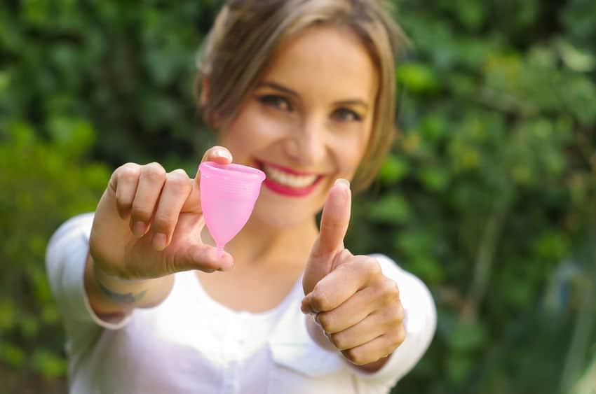 Imagem de mulher segurando coletor menstrual.