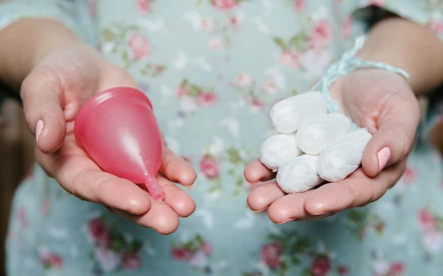 Imagem de pessoa segurando coletor menstrual em uma mão e absorventes internos em outra.