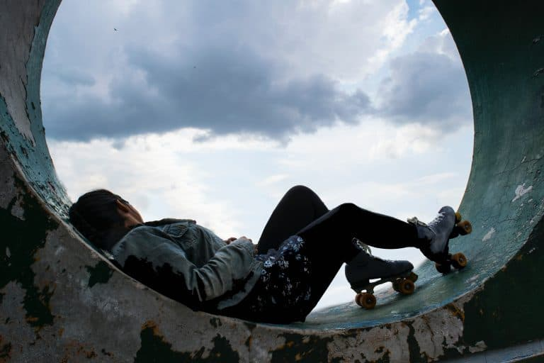Mulher deitada com patins quad.