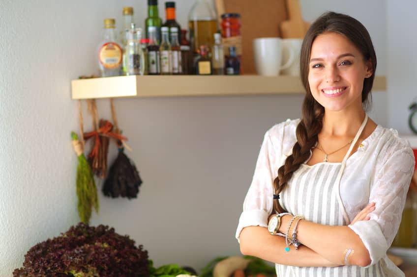 Mulher na cozinha, de braços cruzados e sorrindo