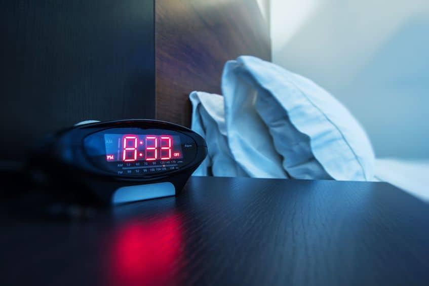 Imagem de despertador digital em cabeceira.