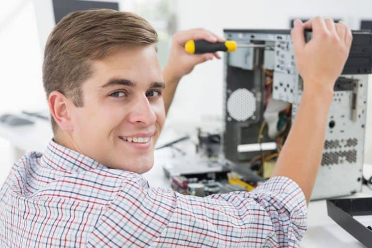 Imagem mostra homem desmontando um computador com uma chave de fenda