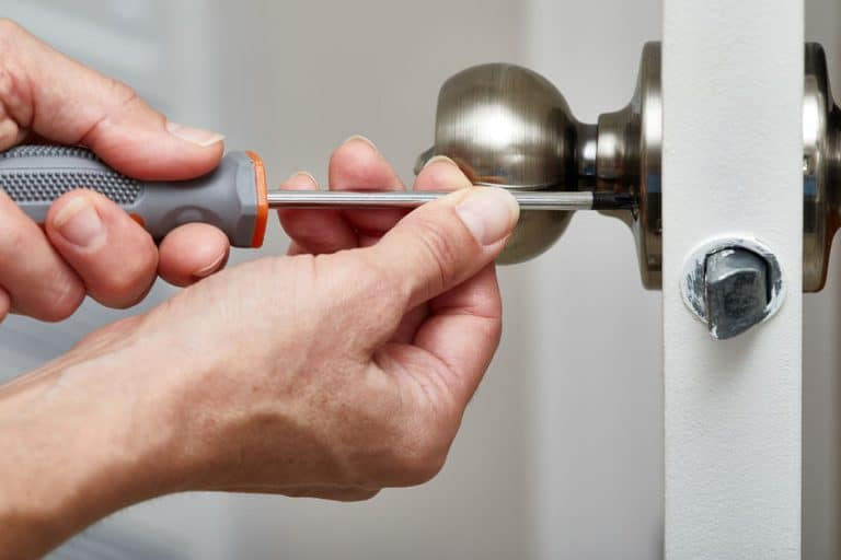 Imagem destaca mão segurando chave de fenda em um trinco de porta