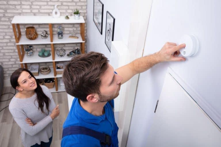 Imagem de homem verificando detector de fumaça e mulher ao fundo.