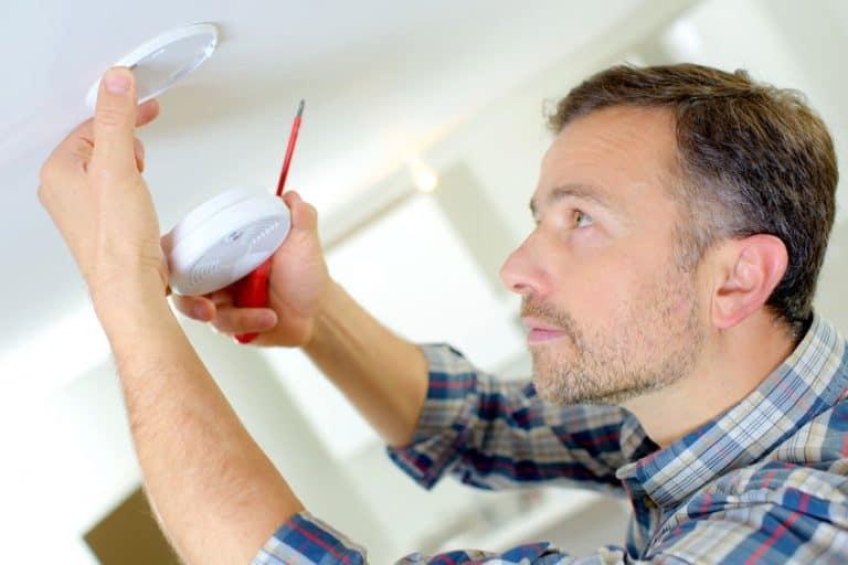 Imagem de pessoa instalando detector de fumaça.