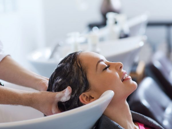 beauty and people concept – happy young woman with hairdresser washing head at hair salon