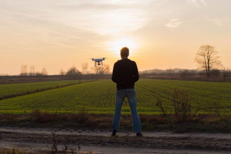 Imagem de homem operando drone em lugar com natureza e sol se pondo.