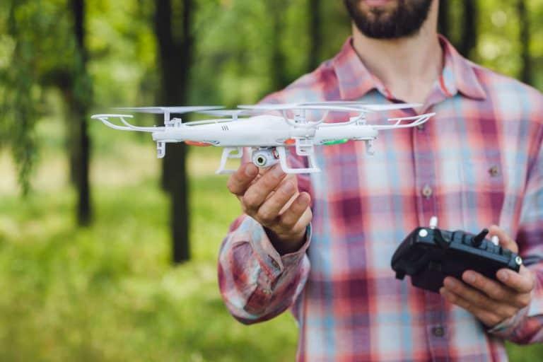 Imagem de homem segurando drone branco e controle.