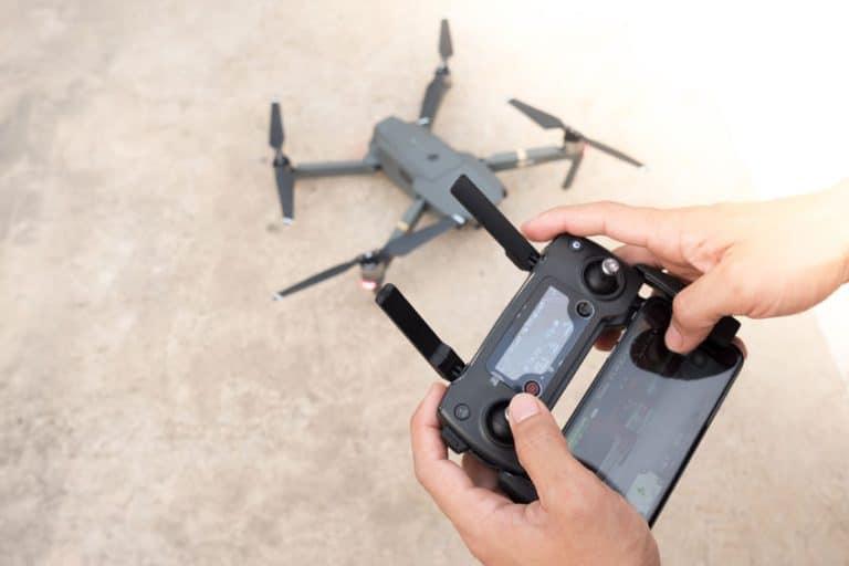 Imagem de pessoa operando controle de drone enquanto o drone está abaixo, no chão.
