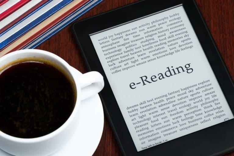 Imagem de e-reader ao lado de xícara de café.