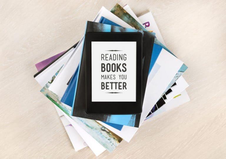 Imagem de livros empilhados com e-reader sobre eles.