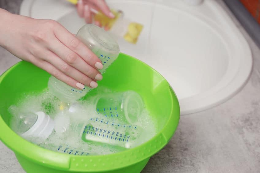Imagem de pessoa lavando mamadeiras.