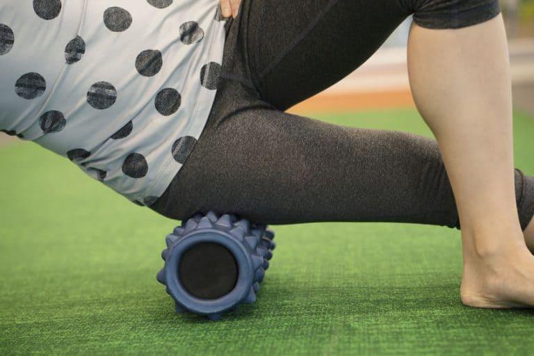 Imagem de pessoa fazendo abdominal lateral com rolo de espuma.