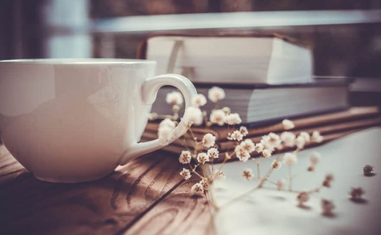 Imagem de xícara de café com livros ao fundo.